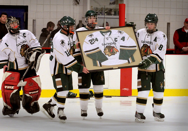 Haverhill: Pentucket hockey players carry the jersey of their teammate Matt McCarthy onto the ice as the number of the late player was retired last night before the team took on Amesbury. Bryan Eaton/Staff Photo