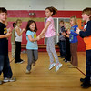 Newburyport: Second-graders Caroline Wollheim, right, jumps up as she and her partner, Lena Ashe, practice their square dance moves at the Bresnahan School in Newburyport on Wednesday morning. The students and Sue Coffey and Cathy Hill's combined gym class were learning traditional American dance. Bryan Eaton/Staff Photo