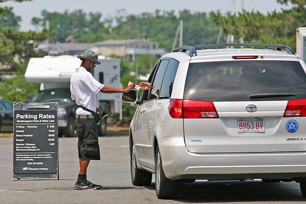 Newburyport: A parking lot attendant accepts the fee from a car at the NRA lot in downtown Newburyport Monday afternoon. Photo by Ben Laing/Staff Photo