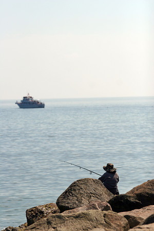 Newbury: A large charter fishing boat sits off of Plum Island as a fisherman tries his luck closer to shore. Photo by Ben Laing/Staff Photo
