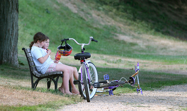 Newburyport: Lili Morris, 10, front, and Eva Mansir, 8, both of Newburyport, take a snack brake as they rode their bikes at the Bartlett Mall Monday afternoon. Photo by Ben Laing/Staff Photo