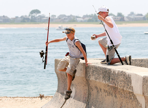 Salisbury: Devon Ruiter, 13, of Hudson, NH, leaps over the sea wall at the Salisbury Beach reservation with this friend, Matt Corning, 13, of Londonderry, NH, in tow. The pair are camping at the reservation and were off to do some fishing Tuesday afternoon. Photo by Ben Laing/Staff Photo