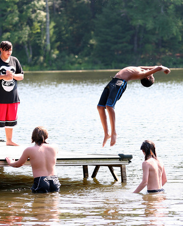 West Newbury: Carlyle Bienaime of Haverhill does a back flip into Mill Pond in West Newbury Monday afternoon as he and his friends looked to cool down on the way home from the Newburyport Skate Park. Photo by Ben Laing/Staff Photo