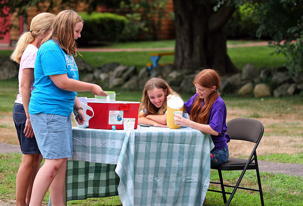 Newbury: Cecilia Shelter, 10, pours a cold cup of lemonade for Malana Stickney, 11. Cecilia and her friend Sandra Jankowski, center, set up their lemonade stand on Hanover Street in Newbury Tuesday afternoon. Photo by Ben Laing/Staff Photo