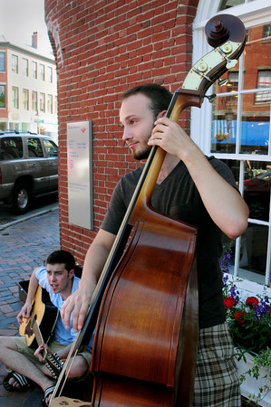 "Newburyport: Sean O'Sullivan, left, and Marc Hoffman, both of Georgetown, play for passersby in Newburyport's Market Square yesterday afternoon. The two are part of the band ""The Truzoos"" playing a mix of rock-n-roll and reggae. Bryan Eaton/Staff Photo"