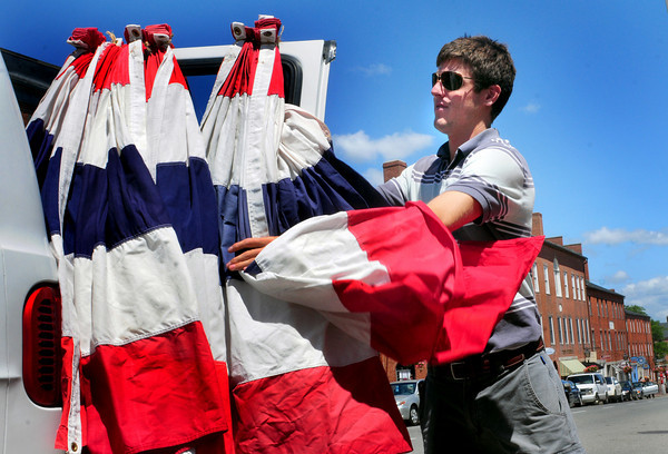 Newburyport: Kyle Mooers of Union Flag Co. pulls bunting off his van to be hung around downtown Newburyport yesterday as the city gets ready for Yankee Homecoming which starts this weekend. Bryan Eaton/Staff Photo