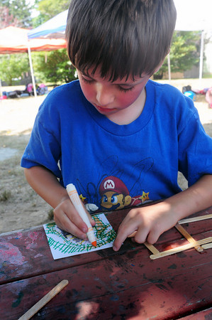 Amesbury: Christopher Lamontt, 6, creates a picture of a train on railroad tracks at the Amesbury Recreation Department's Summer Program. Children also made a frame out of popsicle sticks for their artwork. Bryan Eaton/Staff Photo