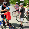 Salisbury: Salisbury police officer Mike Alder shows children how to properly attach their bicycle helmets at a safety talk at a summer program at Salisbury Elementary School on Tuesday. The department used public safety grant money to buy the children new helmets that needed them. Bryan Eaton/Staff Photo