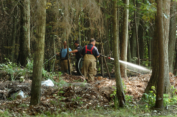 Salisbury: Salisbury firefighters check out hot spots from a small fire that started in some brush in the woods on Erica Way, off Locust Street on Tuesday afternoon. The recent lack of rain has left many lawns brown. Bryan Eaton/Staff Photo