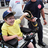 Newburyport: Joe Miller hands a dollar bill to Newburyport firefighter Jeff Cutter, who is collecting for the Muscular Dystrophy Association in Market Square as Joe's dad, Eric, looks on. The Haverhill youngster is the Massachusetts Goodwill Ambassador for the MDA and stopped by to cheer on and thank the Newburyport Firefighters who collect for the organization every Yankee Homecoming. Bryan Eaton/Staff Photo