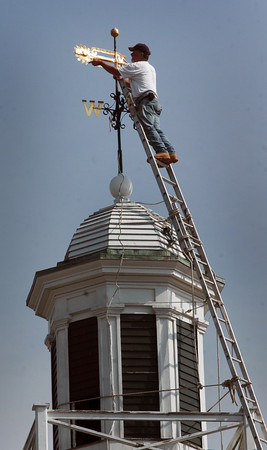 Salisbury: Steeplejack George Burgess of Rockport, Maine, formerly of Byfield, reattaches the weathervane and housing atop the East Parish Meetinghouse in Salisbury Square on Thursday morning. The inch-and-a-half pole holding the vane was bent by the fierce winds in March at the ball where there was some rot. Bryan Eaton/Staff Photo