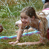 Amesbury: Victoria Griffin, 10, crawls through streams of water at Amesbury Town Park yesterday afternoon cooling off from the heat. She was attending the first day of the town's Recreation Department's Summer Program. Bryan Eaton/Staff Photo