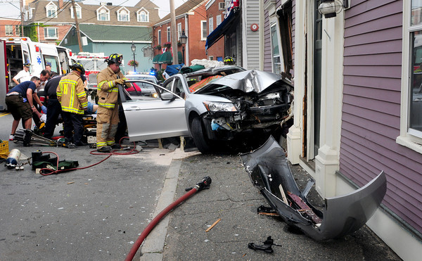 Newburyport: A 78-year-old man is taken from his vehicle that crashed into this building on Water Street in Newburyport yesterday morning next to the Starboard Galley. Firefighters used the jaws of life to extricate the man before being taken to the hospital. Bryan Eaton/Staff Photo