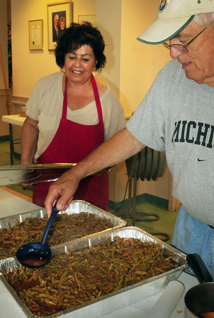 Newburyport: Don Smith ladles tomato sauce from one tin of green beens to another as he and Rena Monoxelos package them to refrigerate overnight. They were two of many volunteers helping to prepare for the Annunciation Greek Orthodox Church's annual Greek Food Festival which begins tonight and goes through Sunday. Bryan Eaton/Staff Photo