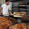 Salisbury: Annarosa's co-owner Bill Malatesta moves bread from their new oven to cooling racks in the company's new Salisbury location. Bryan Eaton/Staff Photo