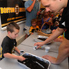 Byfield: James Tatro, 7, of Salisbury plants a seed with Bruin's prospect Ryan Spooner at the Newbury Library Friday. The library won a Bruin's Reading room as part of the Bruin's summer reading program. Jim Vaiknoras/Staff photo