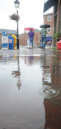 Newburyport: A couple with umbellas walks along a rain soaked State Street in Newburyport Wednesday afternoon. Jim Vaiknoras/Staff photo