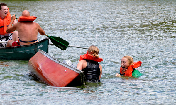 Newburyport: Jessie Uhlig and Phoebie Lanham enjoy the waters of the Frog Pond as Jim and John Gorman sail off victorious after their battle in the canoe tilt at Old-Fashioned Sunday on the Bartlet Mall In Newburyport. Jim Vaiknoras/Staff photo