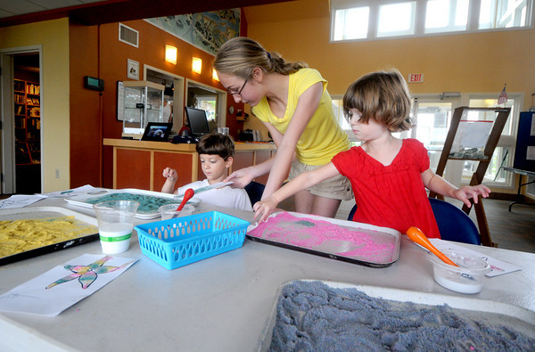 Newburyport: Volunteer Katie Royce makes a starfish carft with glue and sand with Bram Crain, 4 and his twin sister Mabel, at the Joppa Flats Education Center in Newburyport Wednesday.  The center has drop in hours were kids can learn about marine life. Jim Vaiknoras/Staff photo
