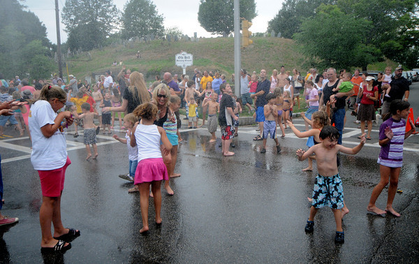Newburyport: Kids and adults cool off in the spray from the annual muster on Pond Street at Old-Fashioned Sunday in Newburyport. Jim Vaiknoras/Staff photo