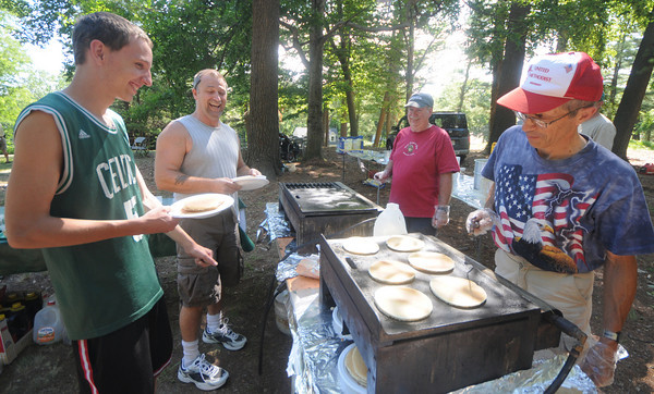 Amesbury: Jack Plante and Bub Ellis wait for pancakes to be cooked by Mark Purdy and Tom Hodges at the annual Pancakes Under the Pines Sunday at Amesbury Park. Jim Vaiknoras/Staff photo