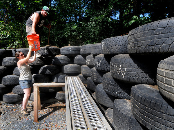 Georgetown: Erica Temple and Aaron Colvan build garage wall made out of used tires at the home of Joe Hull and Elizabeth Rose in Georgetown. Jim Vaiknoras/Staff photo