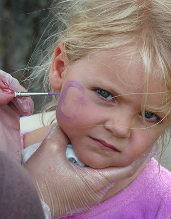 Newburyport: Waters Lloyd, 3, gets her face painted by Claire Dumond at the Newburyport Mother's Club party at Cashman Park yesterday afternoon. The club presented a $5,000 check to the Newburyport Planning Department's Geordie Vining to be used towards the Rail Trail. Bryan Eaton/Staff Photo