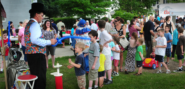 Amesbury: Joseph Stanton, 5, of Amesbury finally made it to the front of a long line to get a balloon from Mr. Dee at Amesbury Day's Block Party last night as the balloon-maker pretended to knight the boy moving the balloon from shoulder to shoulder. Bryan Eaton/Staff Photo