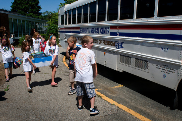 Newburyport: Second-graders from the Bresnahan School in Newburyport carry care packages they put together for troops on a bus the Veteran's Hospital in Bedford. The children got to ride to the hospital to deliver the packages in person. Bryan Eaton/Staff Photo