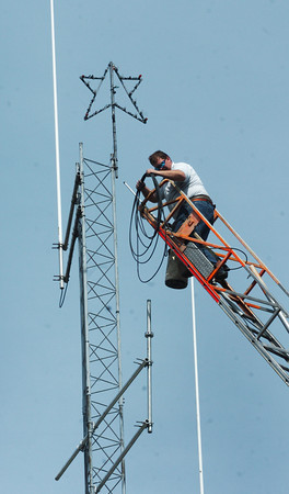 Amesbury: Jamie Clark, fire alarm superintendent for the Amesbury Fire Department used the ladder truck to get up to the top of the communications tower at the station. He was extending the antennae used for the wireless alarm boxes around town yesterday afternoon. Bryan Eaton/Staff Photo