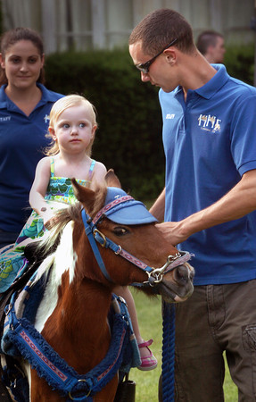Amesbury: Eddie Lemieux of Hunter's Haven Farm in Groveland gives Ani Bienvenue, 2, of Windham, N.H. a pony ride at Amesbury Day's Block Party last night. Her parents are opening the new bakery Zac and Ani's Bread in the Rowell's Block in Amesbury, the former home of Hippie Chick Bakery. Bryan Eaton/Staff Photo