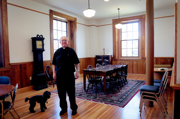 Amesbury: Father Conrad and Abby in the classroom used as a grammar school, though the room has been partitioned and is small. The room is for meetings at the Holy Family Parish Center. Bryan Eaton/Staff Photo