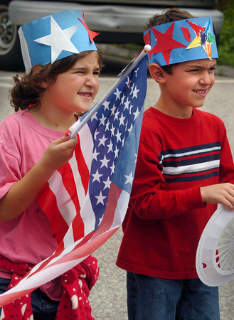Amesbury: Kindergartners Alana DeLisle, left, and Jack Dion, both 6, show their patriotism at Amesbury Elementary School on Monday afternoon. They were having a Flag Day sing-a-long in front of the flagpole attended by parents. Bryan Eaton/Staff Photo