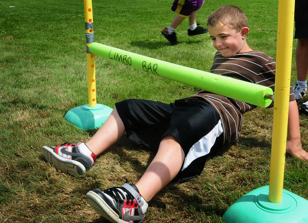Amesbury: Colby Turner, 7, moves under the limbo pole at Amesbury Elementary School's Field Day on Wednesday morning. He was one of a handful of children left to go under at this low level. Bryan Eaton/Staff Photo