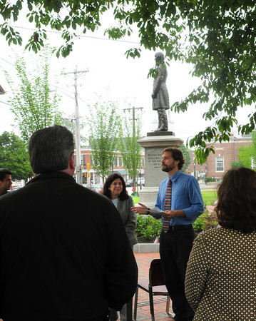 Newburyport: Gordie Vining of the Newburyport Planning Department speaks to a crowd of about 35 people, who huddled under the giant cherry tree as it started to drizzle, at Brown Square. Vining, Mayor Holaday, left, and others involved in the restoration of the square gathered for celebration of the project yesterday afternoon. Bryan Eaton/Staff Photo
