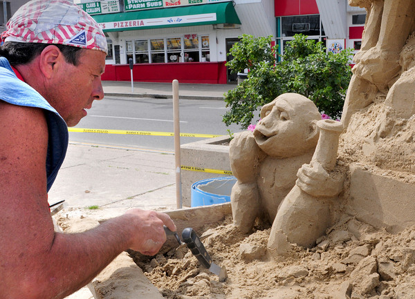 Salisbury: Stephen Topazio of Rhode Island works on a sand sculpture of a tiki house at Salisbury Beach Center. He's one of a handful of sand sculptors working on pieces for next week's Sand and Sea Festival. Bryan Eaton/Staff Photo