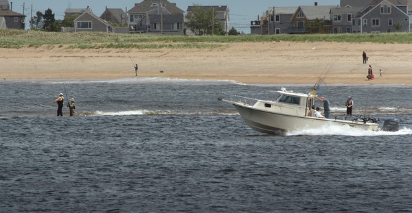 Plum Island: A pleasure fishing boat heads past those casting their lines from the sandbar off Plum Island in the mouth of the Merrimack River on Monday afternoon. Bryan Eaton/Staff Photo