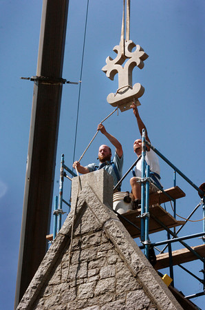 Newburyport: Jeremy Brown, left, and Ray Bourgeois of Richard Irons Restoration Masons from Limerick, Maine lower an 18th-century Victorian finnial atop St. Anna's chapel at St. Paul's Church into place with the assistance of a crane Tuesday afternoon. Three finnials total were put into place as part of the historic church's restoration, funded in part by Community Preservation Funds. Bryan Eaton/Staff Photo