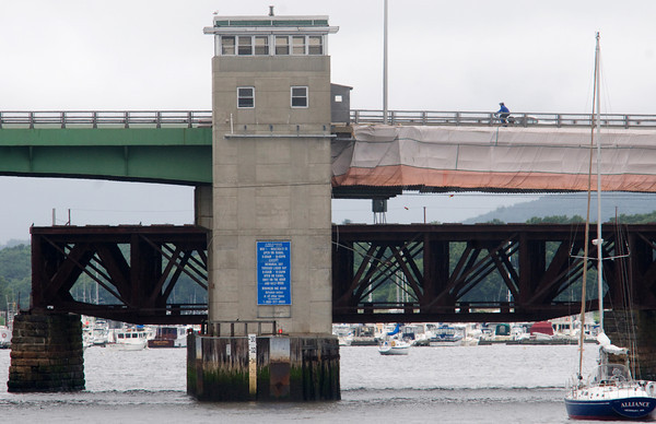 Newburyport: A bicyclist heads over the Gillis Bridge into the wind yesterday afternoon. Fabric can be seen draped underneath them as work continues behind to repaint the north side of the bridge, the south side having been completed. Bryan Eaton/Staff Photo