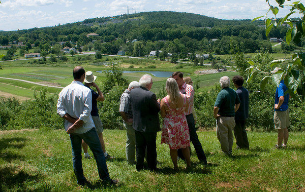 Amesbury: A delegation from Spain, including the Minister of Agriculture, toured Ciderhill Farm in Amesbury to learn about American farming techniques and how farms try to involve customers as with pick-your-own fruit and CSA's. Here owners Glenn and Karen Cook took the group to look over the fields from the apple orchards above. Bryan Eaton/Staff Photo