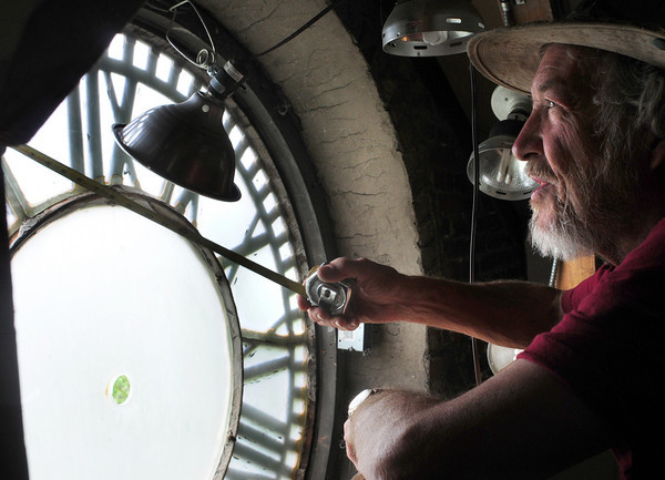 Newburyport: Ed Siegmann of Dovetail Clocks takes measurements of the clock atop the Firehouse Center in Newburyport on Wednesday morning. He removed the hands and mechanical components to repair in his Newburyport shop. Bryan Eaton/Staff Photo