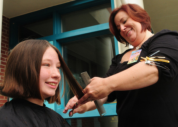 Merrimac: The Donaghue School in Merrimac held their annual Relay for Life as a fundraiser for cancer survivors on Monday. Some donated their hair to make wigs for those in treatment, pictured, Stephanie Beaudoin, 12, getting hers cut by Liz Hume of Absolute Hair Salon of Newburyport. Bryan Eaton/Staff Photo