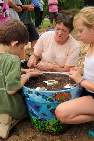 Newburyport: Nancy Earls intructs Jaden Sousa, 7, left, and Macey LaValley, 9, on what seeds to plant in one of four giant painted flower pots. The Newburyport Learning Enrichment Center, is working with Green Artists League, to create a shared community garden with the residents at the Griffin Home for Aged Men. Bryan Eaton/Staff Photo