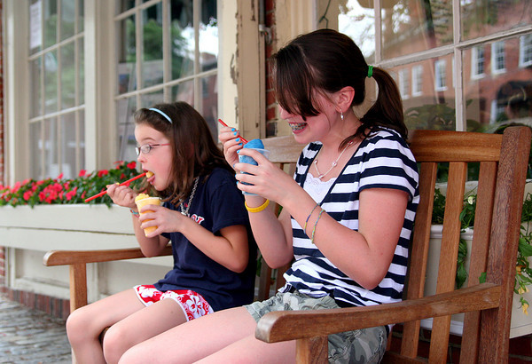 Newburyport: Kate Nickodemus, 12, and her sister Ellen, 8, try to beat the heat with some slush outside Simply Sweet on Inn Street Monday afternoon. Photo by Ben Laing/Staff Photo