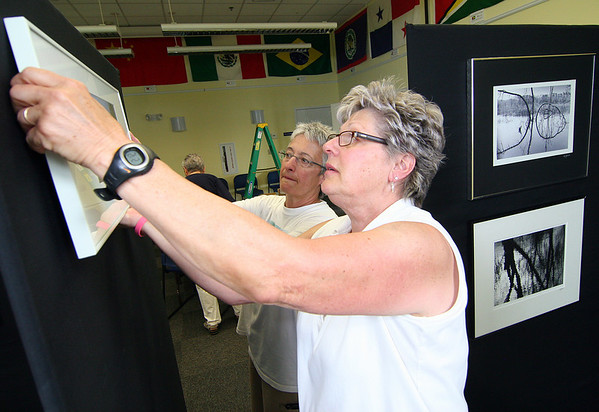 Newburyport: Pearl Racette, left, and Cheryl Proia, right, help hang photographs by Patricia Bashford, local Newburyport artist, who'll have 34 piece on exhibit at the Joppa Flats Nature Center. Photo by Ben Laing/Staff Photo