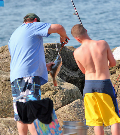 Newbury: Ricky Graff, 14, and his father, Frank struggle to free a flounder they reeled in on Plum Island Monday afternoon. The pair were visiting from Peabody to do some salt water fishing. Photo by Ben Laing/Staff Photo