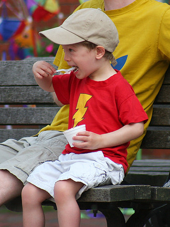 Newburyport: Cedar Schumacher, 3, of Newburyport, scoops a mouthful of ice cream while sitting on a bench at Market Square with his dad Monday afternoon. Photo by Ben Laing/Staff Photo