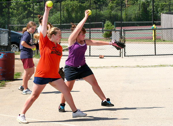 Amesbury: Devin Chigas, 13, left, and Alexis Dupra, 13, both of Amesbury, practice their pitching at Amesbury Middle School Tuesday morning. The girls are participating in the Amesbury Youth Softball Clinic run by Amesbury High School softball coach Chris Perry. The girls were also visited by local softball legend Ashley Waters and her teamates from the Stratford Brackettes. Photo by Ben Laing/Staff Photo