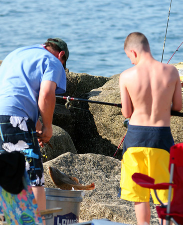 Newbury: Ricky Gaff, 14, and his father, Frank struggle to free a flounder they reeled in on Plum Island Monday afternoon. The pair were visiting from Peabody to do some salt water fishing. Photo by Ben Laing/Staff Photo