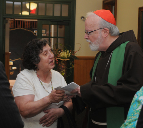 Amesbury: Cardinal Sean O'Malley speaks with a parishioner at the Newbury Parish Center at the Holy Family Church in Amesbury Saturday. Jim Vaiknoras/Staff photo
